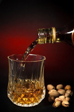 Filling a crystal glass with whisky drink, alcohol, and pistachios, beverage art background, red photo
