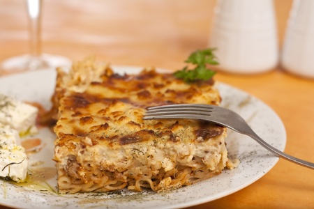 Pastitsio greek food on a table, wine alcohol drink salt, feta cheese and pepper photo