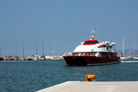 arrive: A red high speed dolphin arrive to the port of Skopelos at Greece. Stock Photo