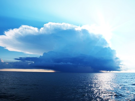 Bright blue sky with stormy clouds over a calm sea photo