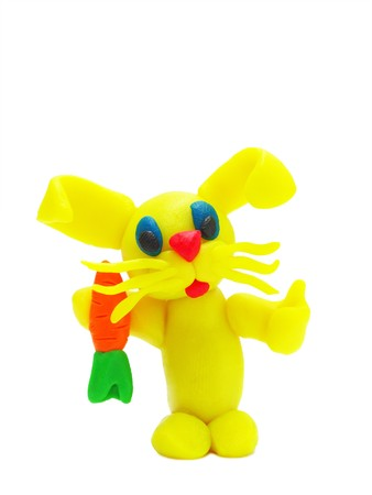plasticine: Funny yellow plasticine rabbit with carrot on white background with soft shadows Stock Photo