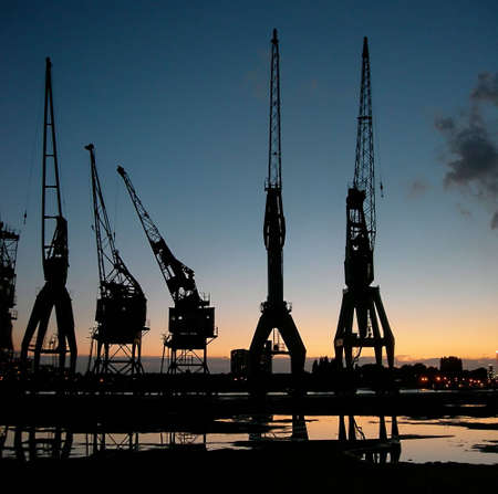 Silhouette of some verry old cranes againt sunset sky in Antwerp, Belgium Stock Photo