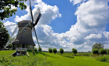 watermanagement: A dutch windmill inside a rural environment Stock Photo