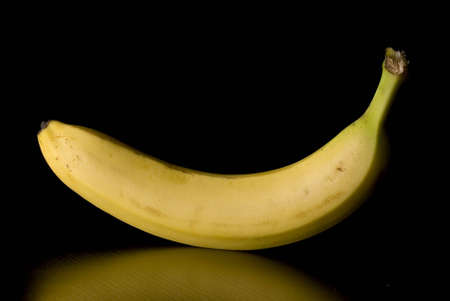 A single banana isolated on a black with reflection
