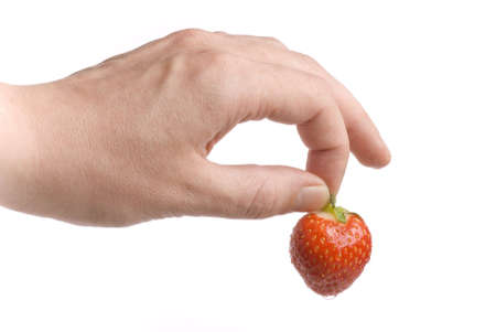 Hand holding a fresh and wet strawberry