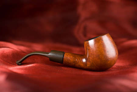 An old smoking pipe isolated over a red fabric