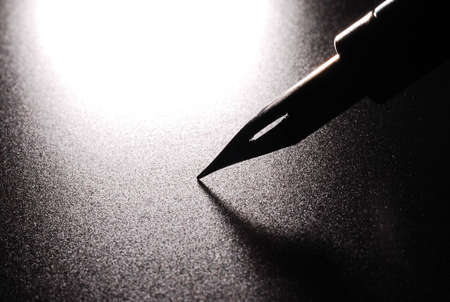 A nib from a dip pen over black Stock Photo