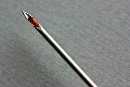 The Sharp point from a medical injection needle over gray