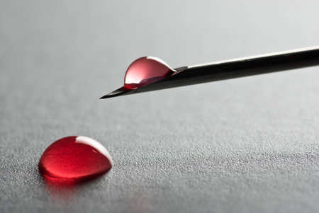 The Sharp point from a medical injection needle with a droplet of blood on gray surface