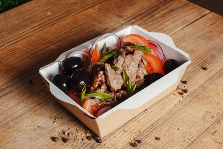 Greek salad of organic vegetables with tomatoes, cucumber, red onion, olives and veal