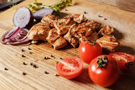 Juicy chicken meat grilled. Close to the kebab lies fresh vegetables and onions.
