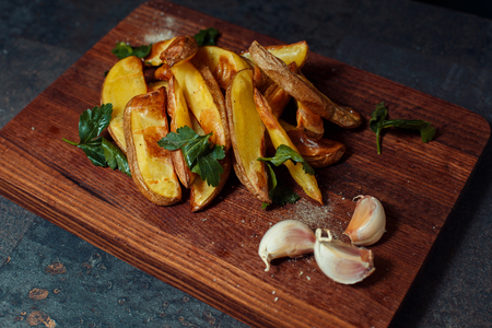 Baked potato slices on a wooden board with spices and garlic.