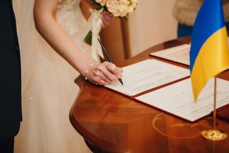 Hochzeitszeremonie. Standesamt. Ein frisch verheiratetes Paar unterschreibt die Heiratsurkunde. Junges Paar unterschreibt Hochzeitsdokumente.