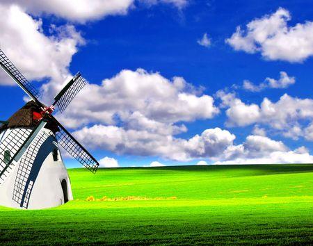 Licht groen veld met Wildmill Stockfoto