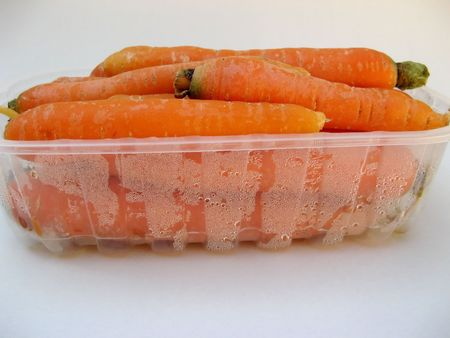 Photo of isolated fresh orange carrots in a plastic box. Stock Photo