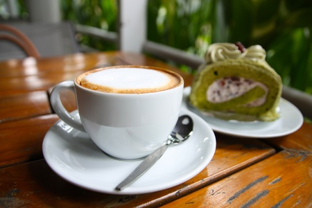 Hot cappuccino coffee with  background of blur cake roll Stock Photo - 10370661