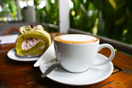 Hot cappuccino coffee with  background of blur cake roll photo
