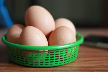 fresh egg in the green basket on the table with blur background photo