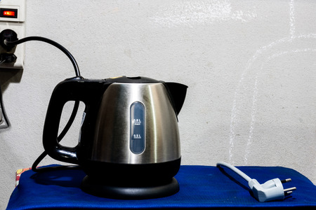 boil water: Background image of electric kettle with plug on the wall. Prepare for boil water.