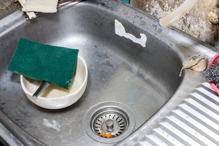 bowl sink: Image of dirty ceramic bowl with scouring pad in dish sink before cleaning