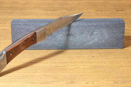 pocket knife: Image of pocket knife with wood handle on the hone for sharpening