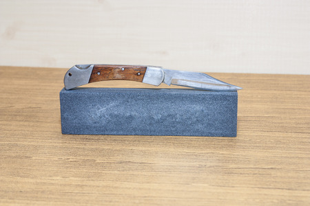 hone: Background image of hone and pocket knife with wood handle.