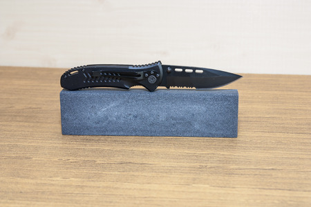 pocket knife: Black steel pocket knife on the carborundum stone.