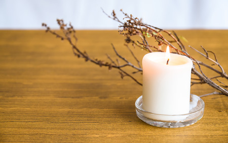 Candle with flame and dry twigs on the table Stock Photo