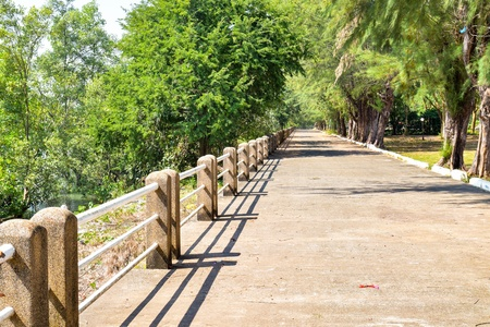 Walkway near the sea is made by concrete and have a fence to protect everyone down to the sea.