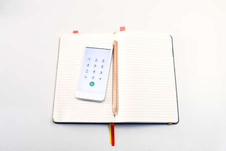Smartphone and pencil in the book on the white table, ready for call and ready for note