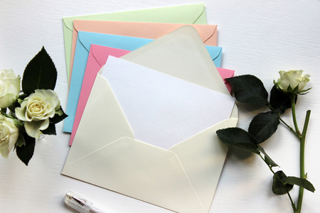 흰 장미와 파스텔 색상에서 빈 봉투의 세련 된 Mockup 사진. 브랜딩 ID를위한 템플릿. 평면도. 스톡 콘텐츠