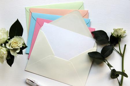 Stijlvolle mockupfoto van lege enveloppen in pastelkleuren met witte rozen. Sjabloon voor branding van identiteit. Bovenaanzicht.