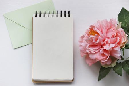 Mockup fotografie met roze pioen, notebook en envelop. Desktop werkplek ontwerper, kunstenaar, schilder bovenaanzicht. Moderne trend sjabloon voor reclame.