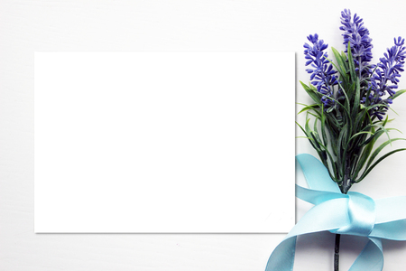 Mockup with Artifical lavender flowers bouquet, blue ribbon and blank paper . Vintage style mockup for your photos and arts