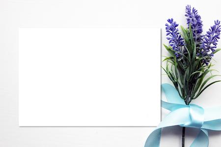 Mockup met Kunstmatige lavendel bloemen boeket, blauw lint en blanco papier. Vintage stijl mockup voor uw foto's en kunst Stockfoto