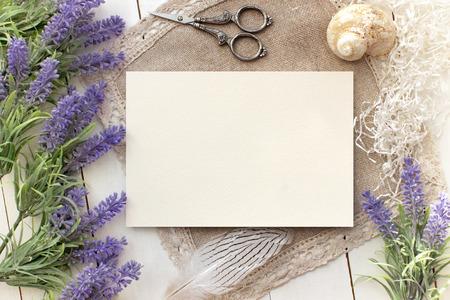 Kunstmatige lavendel bloemen en blanco papier mockup. Vintage stijl mockup voor uw foto's en kunst. Franse Provence Europese stijl Stockfoto