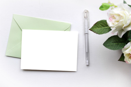 Mock-up for presentations with roses, green envelope and a card. Desktop workplace designer, artist, painter top view. Modern trend template for advertising.