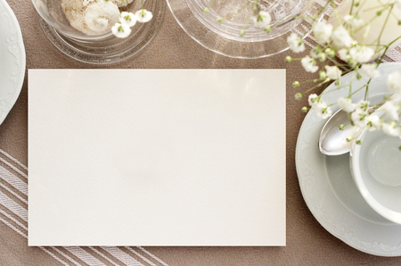 vintage tea invitation mockup. Blank card on a table with vintage dishes for tea Archivio Fotografico