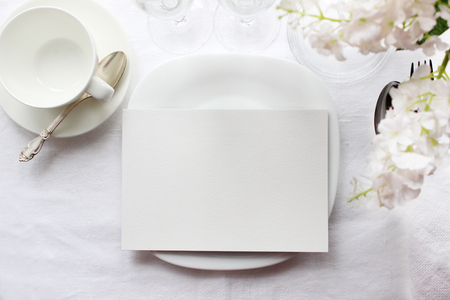 Table card mockup, menu mockup. Wedding fashion photography. Wedding invitation. Place card, reserved card. White beautiful dishware. Trendy white colors stylish photo. Archivio Fotografico