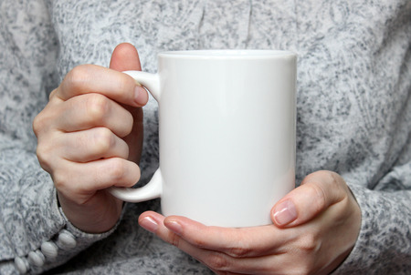 Girl is holding white cup in hands. White mug in womans hands. Mockup for designs.