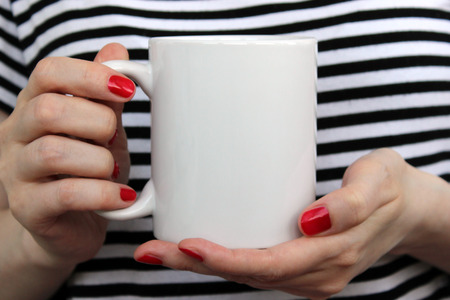 La muchacha está sosteniendo la taza blanca, una taza en las manos. Maqueta de diseños. Foto de archivo