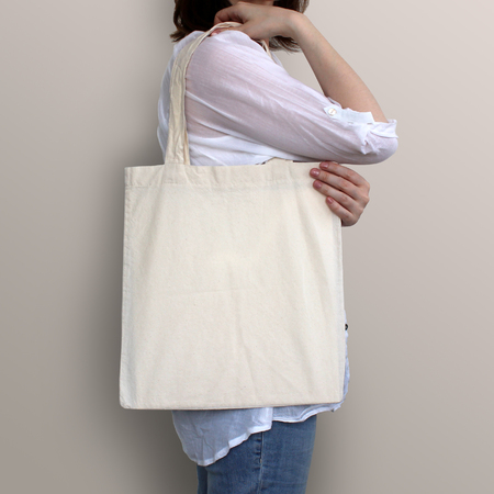Girl is holding blank cotton eco bag, design mockup. Handmade shopping bag for girls. Stock Photo