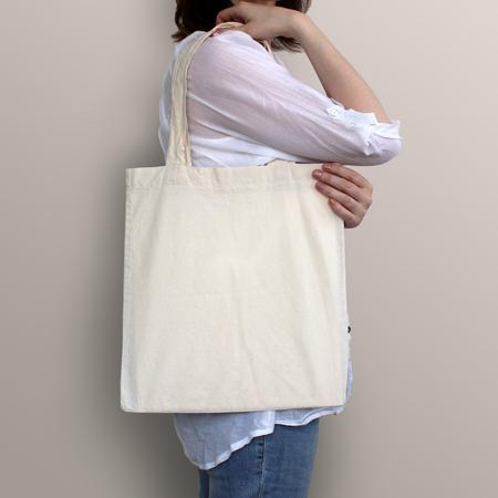linen bag: Girl is holding blank cotton eco bag, design mockup. Handmade shopping bag for girls. Stock Photo
