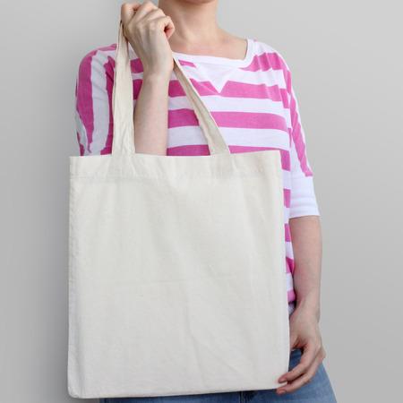 La muchacha está sosteniendo la bolsa ecológica de algodón blanco, maqueta de diseño. bolsa de la compra hecha a mano para las niñas.