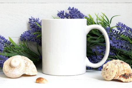 Mock-up of a white mug with lavender and seashells. Stock Photo