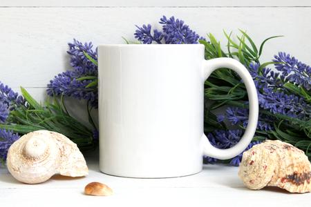Mock-up van een witte mok met lavendel en schelpen.