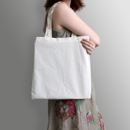 La muchacha está sosteniendo la bolsa de asas de algodón ecológico en blanco, maqueta de diseño. bolsa de la compra hecha a mano para las niñas.