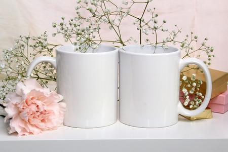 Two white mugs, cups wedding mockup. Gypsophila, carnation, gifts on the background. Pastel colors Reklamní fotografie