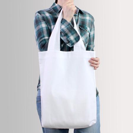 여자는 흰색 빈 면화 tote 가방, 디자인 mockup을 잡고있다. 소녀를위한 수제 쇼핑백. 스톡 콘텐츠