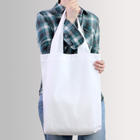 Girl is holding white blank cotton tote bag, design mockup. Handmade shopping bag for girls. Archivio Fotografico